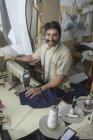 Schneidermeister arbeitet in Werkstatt an Nähmaschine, Schneiderzubehör hängt herum — Stockfoto