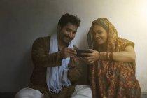Усміхнене пара, сидячи на підлозі і використання мобільного телефону — стокове фото