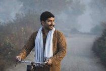 Agriculteur sur la route de campagne tenue cycliste et en regardant loin matin brumeux — Photo de stock