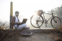 Farmer sitting near agriculture field and using laptop computer — Stock Photo
