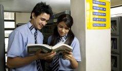 Niño y niña leyendo un libro en una biblioteca - foto de stock