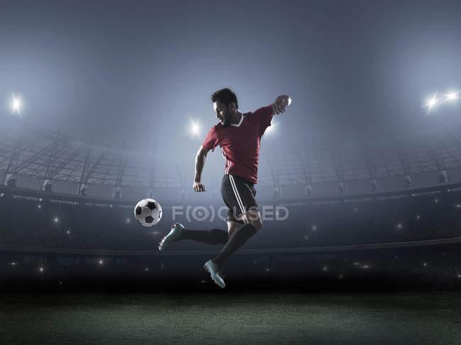 Jugador de fútbol que muestra habilidad con la pelota en el estadio - foto de stock