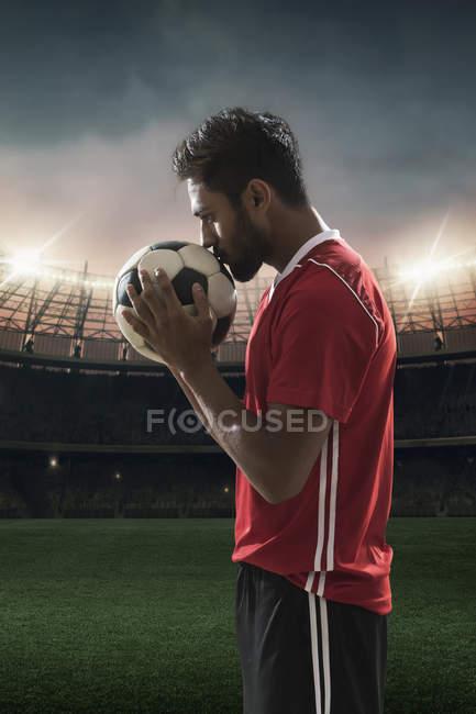 Футболист целует футбол со стадионом на заднем плане — стоковое фото