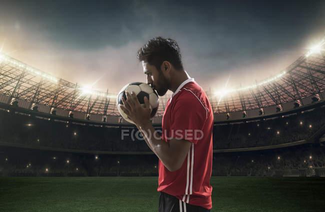Jugador del balompié de besos fútbol con estadio en el fondo - foto de stock