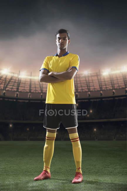 Retrato de pie de jugador de fútbol con estadio en el fondo - foto de stock