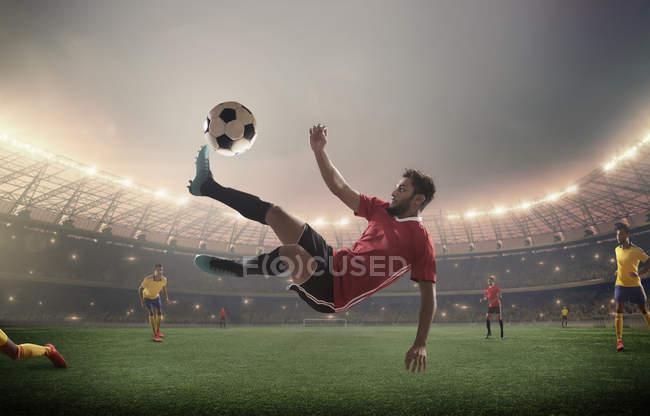 Bicicleta de jugador de fútbol pateando el fútbol - foto de stock