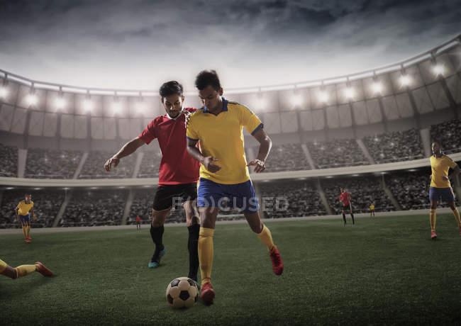 Futbolistas rivales en un reto para la posesión del fútbol - foto de stock