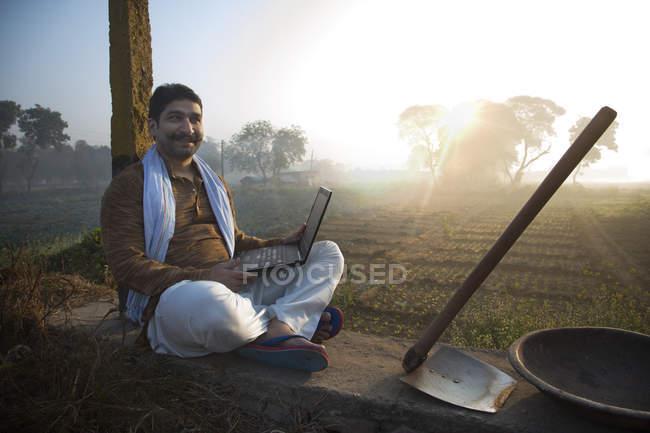 Landwirt Landwirtschaft Nahfeld sitzen und Laptopcomputer — Stockfoto