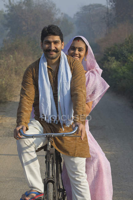 Casal rural feliz em vestido tradicional andando de bicicleta na estrada de campo — Fotografia de Stock