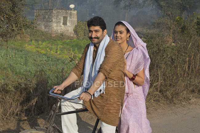 Happy rural couple in traditional dress riding on bicycle at country road — Stock Photo