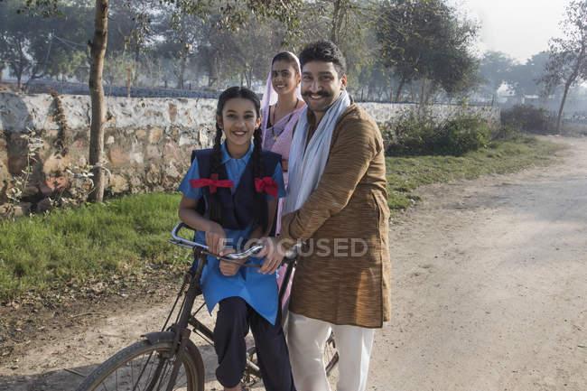 Famiglia rurale felice con bicicletta in strada villaggio — Foto stock
