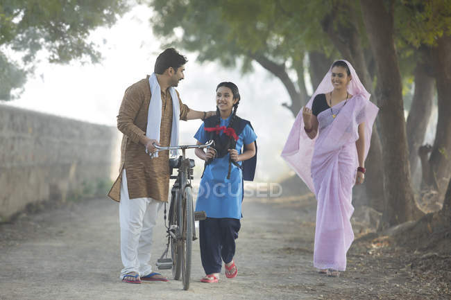 Happy rural couple with daughter walking on village street — Stock Photo
