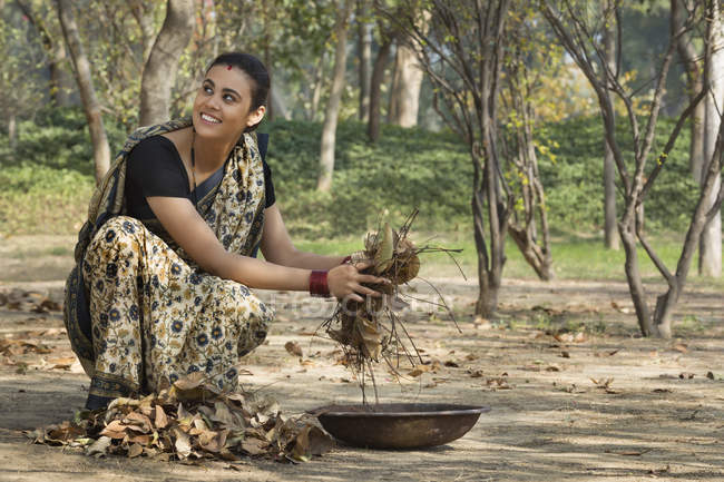 Indian woman dressed in sari collecting dried leaves from ground in iron gold pan — Stock Photo