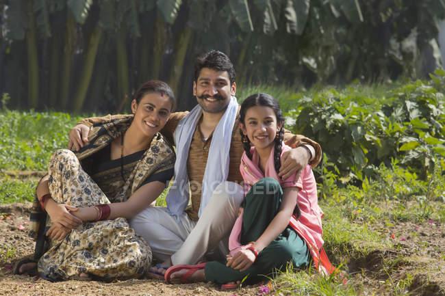 Sourire de famille indienne assis sur le domaine de l'agriculture — Photo de stock