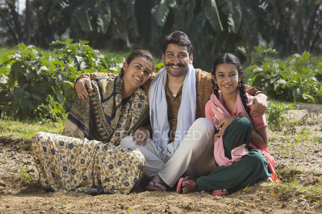 Smiling Indian family sitting on agriculture field — Stock Photo