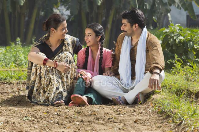 Sorrindo Família indiana sentada no campo agrícola — Fotografia de Stock