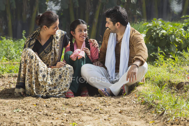 Smiling Indian family sitting in agriculture field — Stock Photo