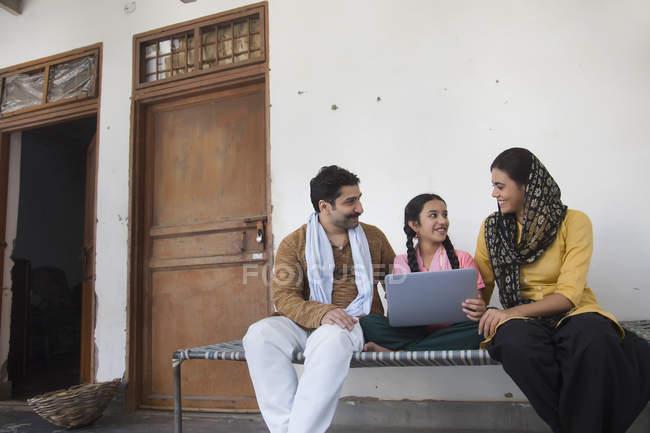 Menina indiana sentada com os pais no berço e usando computador portátil — Fotografia de Stock