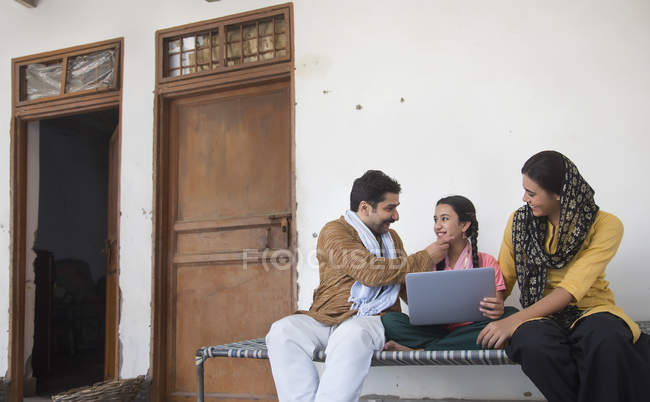 Indian girl sitting with parents on cot and using laptop computer — Stock Photo