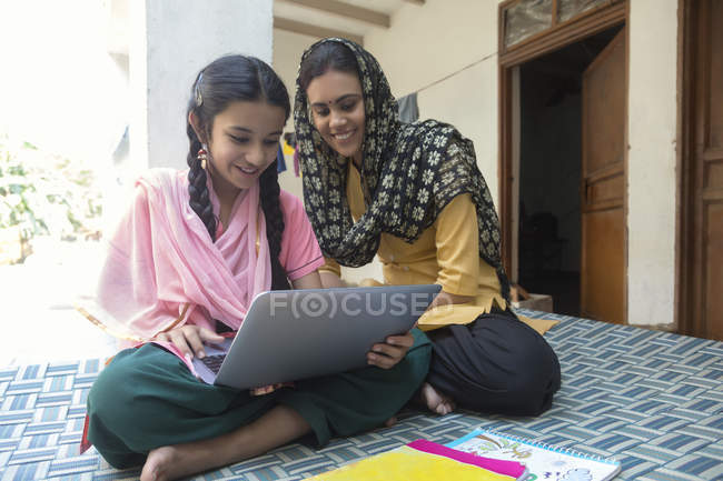 Woman sitting with daughter on cot at home and using laptop — Stock Photo