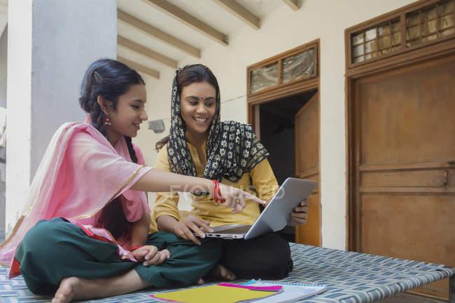 Donna seduta con figlia sul lettino a casa e utilizzando il computer portatile — Foto stock