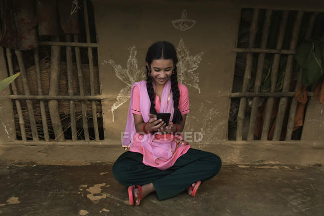 Indian village girl sitting in rural house and using mobile phone — Stock Photo