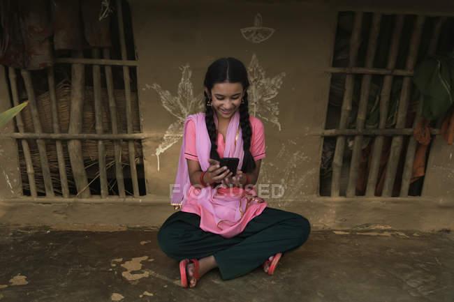 Indien fille de village assis dans la maison rurale et en utilisant un téléphone mobile — Photo de stock
