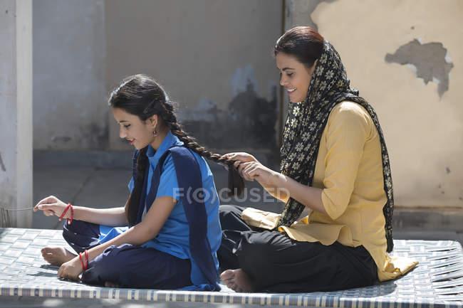 Donna treccia capelli di figlia seduta su culla in casa — Foto stock