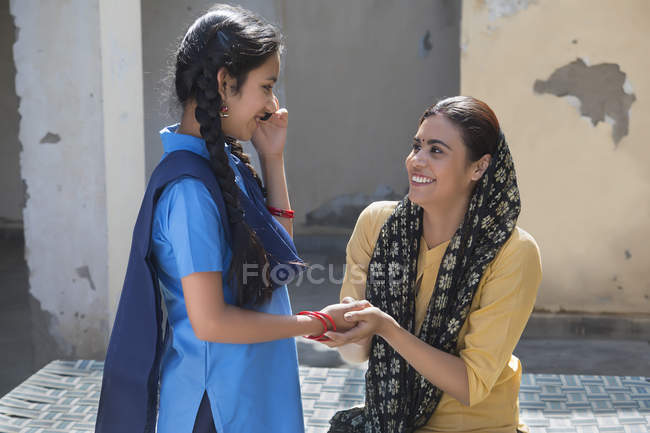 Indian girl talking at mobile phone when holding mother hand — Stock Photo