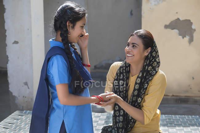 Fille indienne parler au téléphone mobile lors de la tenue de la main mère — Photo de stock