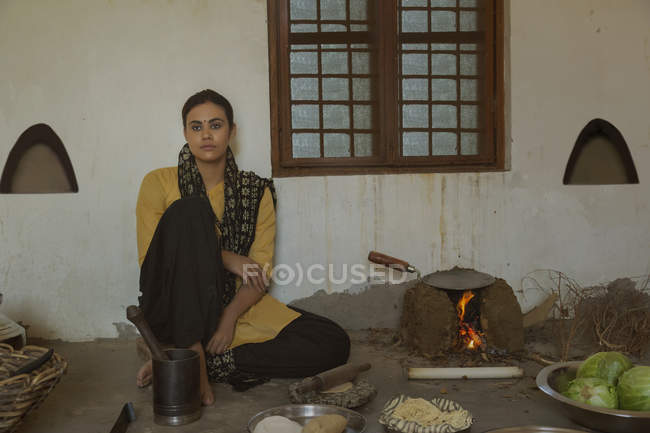 Indian woman sitting in kitchen on floor — Stock Photo