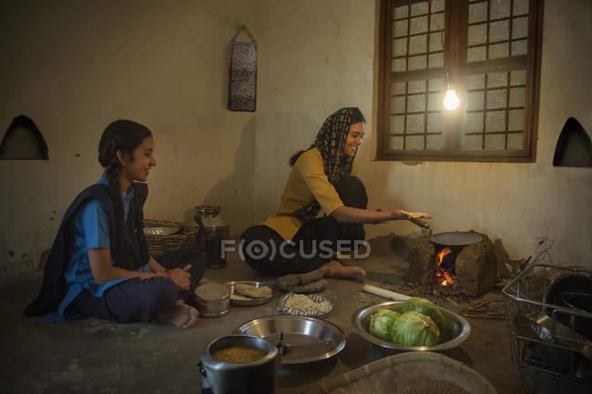 Індійська сільська жінка сидить на кухні та приготування їжі на дров з посудом і овочі на підлозі і розмовляти з дочкою — стокове фото