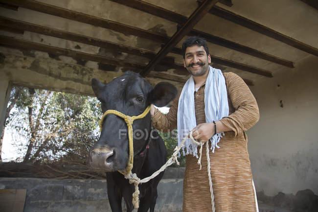 Lächelnde indischen männlichen Bauern in der Nähe von schwarzen Kuh im Stall — Stockfoto