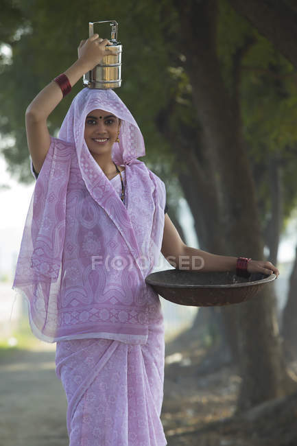 Indian woman carrying tiffin box on head and iron gold pan in hand — Stock Photo