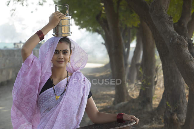 Mujer India de tiffin caja en pan de oro hierro y cabeza que lleva en la mano - foto de stock