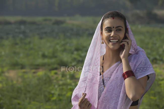 Retrato de mulher rural sorridente cobrindo cabeça com sari falando ao telefone contra campo de fazenda — Fotografia de Stock