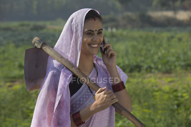 Portrait of smiling woman carrying spade on shoulder and talking over mobile phone — Stock Photo