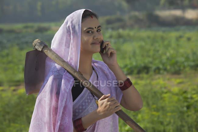 Ritratto di donna sorridente che porta vanga a spalla e parla al cellulare — Foto stock