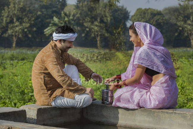 Indian couple sitting near water tank in agriculture field — Stock Photo