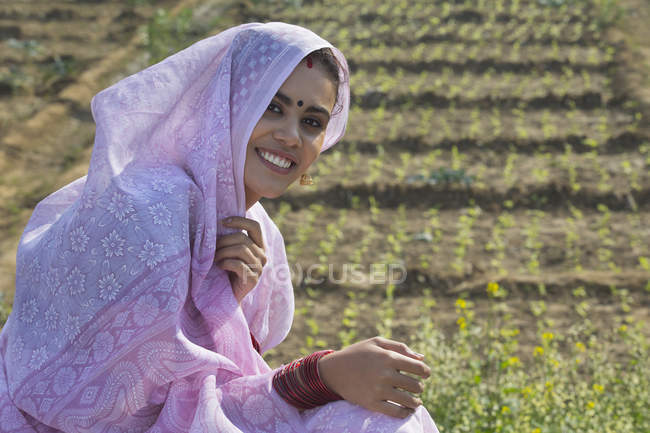 Portrait of smiling rural woman covering head with sari sitting at field — Stock Photo