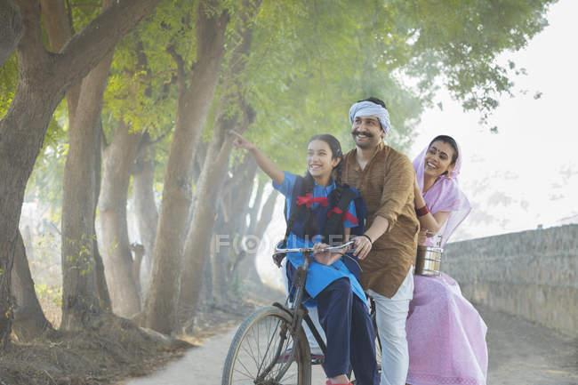 Feliz casal rural, juntamente com a filha andando de bicicleta na aldeia — Fotografia de Stock