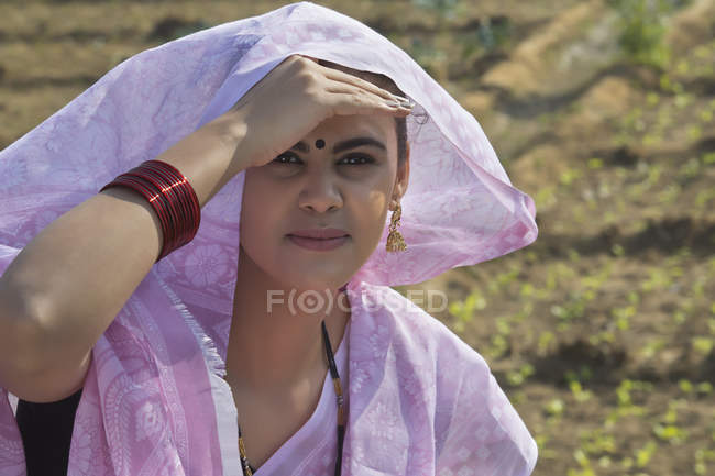 Portrait of woman in pink sari sitting near agriculture field — Stock Photo