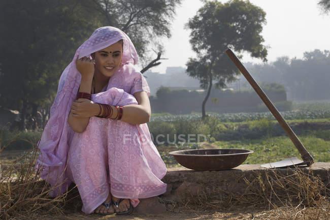 Donna in sari rosa seduta vicino al campo agricolo — Foto stock