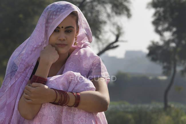 Ritratto di donna in sari rosa seduta vicino al campo agricolo — Foto stock