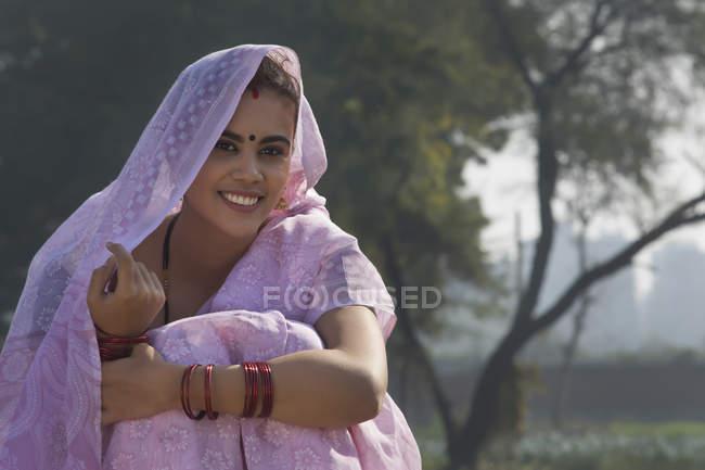 Close-up de uma mulher rural sorridente sentado perto do campo agrícola cobrindo a cabeça com saree — Fotografia de Stock