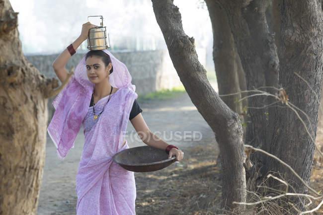 Mulher indiana carregando caixa de tiffin na cabeça e ferro panela de ouro na mão — Fotografia de Stock