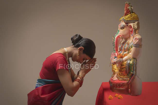 Frau betet mit geschlossenen Händen und geschlossenen Augen vor Ganpati-Idol — Stockfoto
