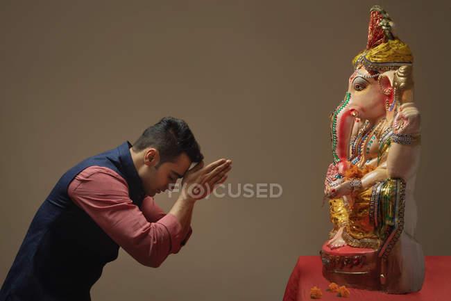 Juntou-se homem rezando com mãos e olhos fechados em frente do ídolo Ganpati — Fotografia de Stock