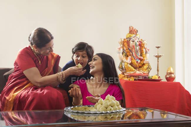 Індійська сім'ї в святковий одяг і традиційних продуктів харчування на скляному столі — стокове фото