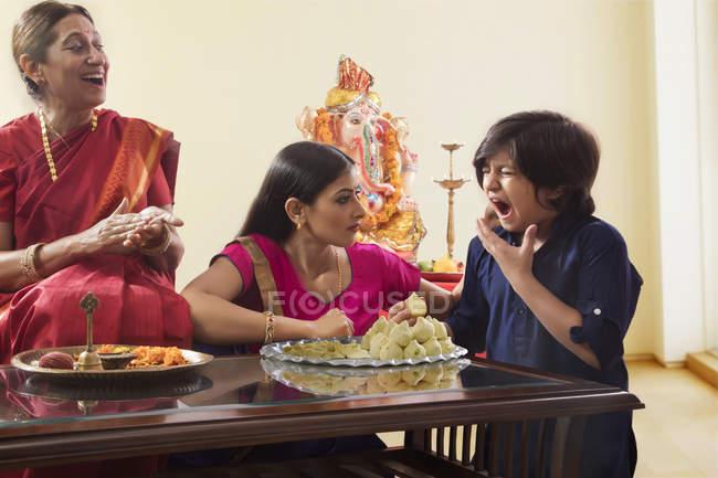 Indische Familie in festliche Kleidung und traditionelle Küche auf Glastisch — Stockfoto